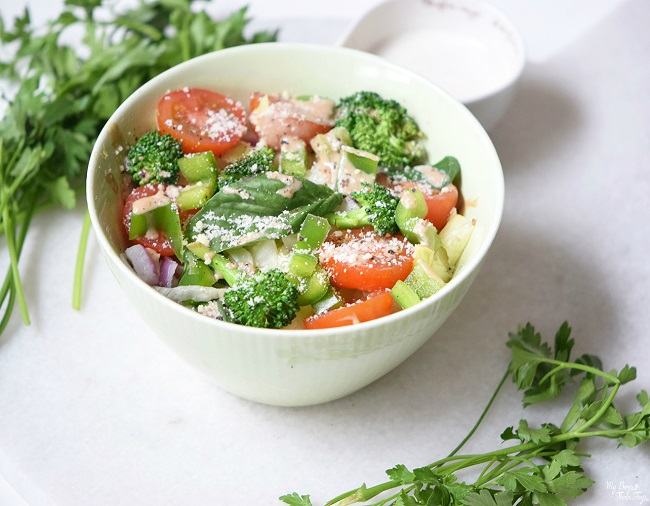 Broccoli Salad in white bowl with dressing
