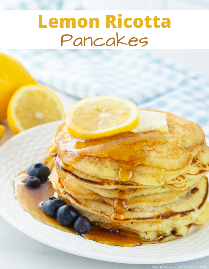 lemon ricotta pancakes with syrup drizzle, blueberries and lemon on top.