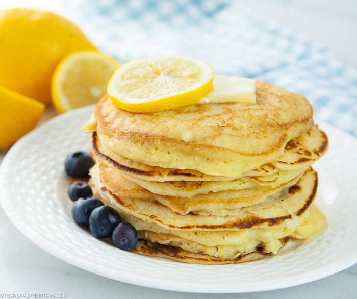 lemon ricotta pancakes with butter, sliced lemon and blueberries on white plate.