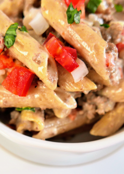 beef pasta tomato onions penne in white bowl